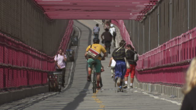 vídeos de stock, filmes e b-roll de people ride their bikes over the bike path of the williamsburg bridge going from brooklyn to manhattan. - williamsburg new york