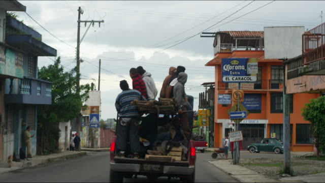 People ride through Mexican town in back of pick-up truck