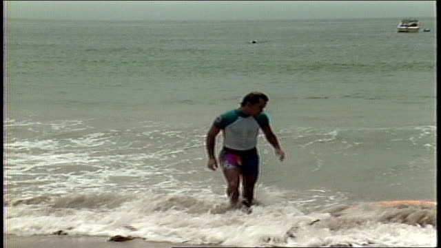 people riding and jumping waves on skimboards - anno 1987 video stock e b–roll