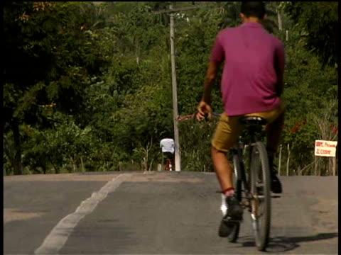 vídeos y material grabado en eventos de stock de ms, tu, people riding bicycles toward nuestra senora de la caridad del cobre, santiago de cuba  - sólo hombres jóvenes