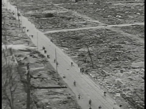 people riding bicycles walking on road lined w/ flat rubble landscape ws block w/ partial building standing ws leaning building w/ telephone pole... - 1945点の映像素材/bロール