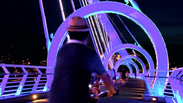 people riding bike on yangguang bridge at dusk, new taipei, taiwan - taipei stock videos & royalty-free footage