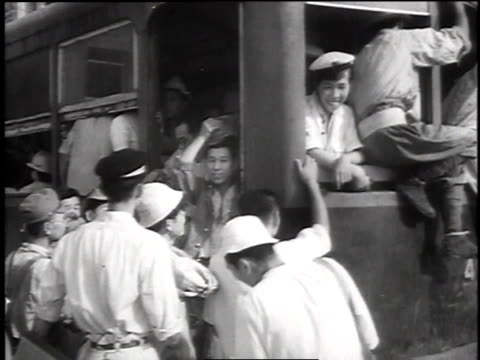 people riding bikes and boarding crowded streetcar / passengers hanging on outside of streetcar - 1945点の映像素材/bロール