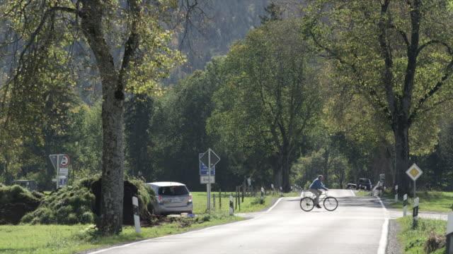 people riding bikes cross streets as cars drive by - verkehrsschild stock-videos und b-roll-filmmaterial