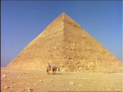 2 people riding camel in desert with pyramid in background / egypt - arbeitstier stock-videos und b-roll-filmmaterial