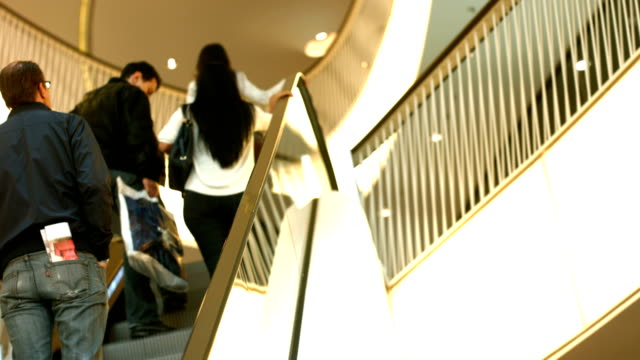 stockvideo's en b-roll-footage met people riding escalator in shopping mall (4k/uhd to hd) - overexposed
