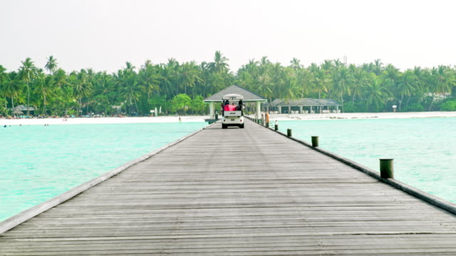 ms people riding golf cart on tropical dock,maldives - golf cart stock videos & royalty-free footage