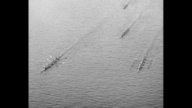 People riding observation train to rowing contest / overhead shot from bridge of rowers racing down river in shells / shot from moving observation...