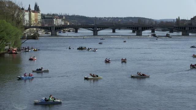 ws people riding paddle boats on river near charles bridge / prague, hlavni mesto praha, czech republic - charles bridge stock videos & royalty-free footage