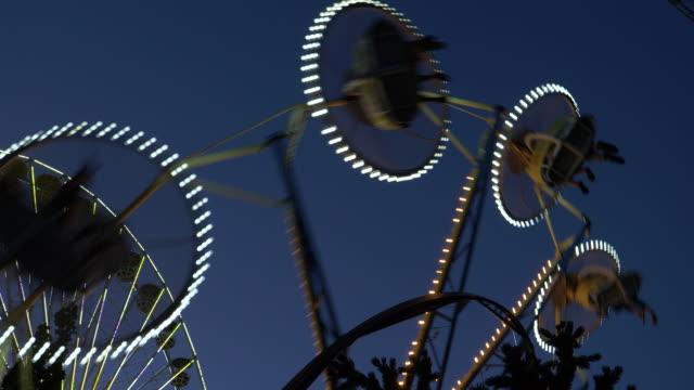 People riding spinning amusement park ride at night / Salt Lake City, Utah, United States