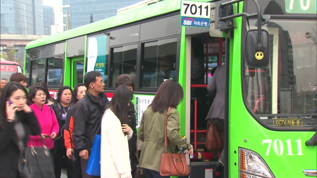 people riding the bus, the bus transit center in seoul - バス停留所点の映像素材/bロール