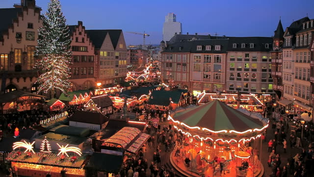 WS People roaming and enjoying at Christmas market at Romer Square at night / Frankfurt, Main, Hesse, Germany