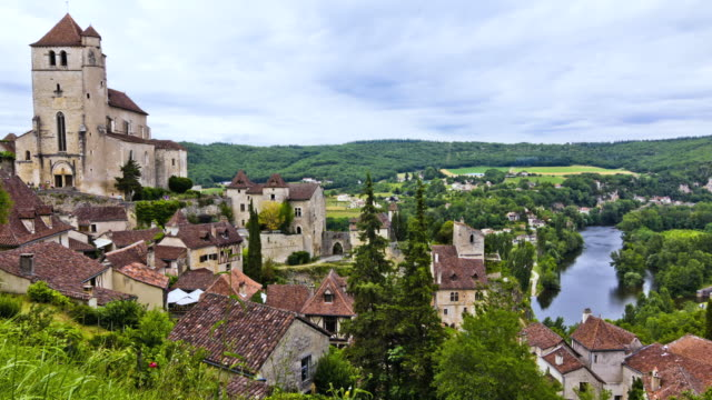 WS T/L TU People roaming at fortified church near Lot river in village / Saint-Cirq-Lapopie, Midi-Pyrenees, France