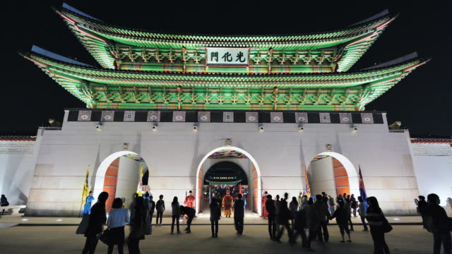 ms t/l people roaming at gwanghwamun gate (gyeongbokgung royal palace's entrance gate) at night / seoul, south korea - 史跡めぐり点の映像素材/bロール