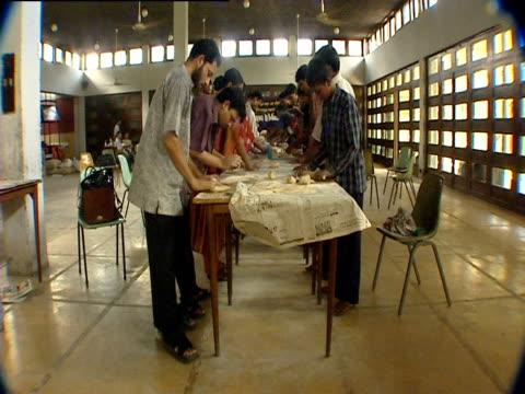 vídeos de stock, filmes e b-roll de people roll out dough for roti on a long table - rolo de pastel