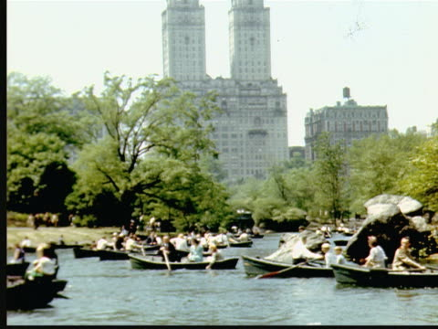 1947 montage people rowing rowboats on lake in central park on beautiful summer day. san remo apartment building in background / new york city, usa - remo stock videos and b-roll footage