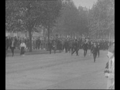 people run in street as crowd stands in background / soldiers march during a demonstration of national socialist german worker's party supporters in... - ナチズム点の映像素材/bロール