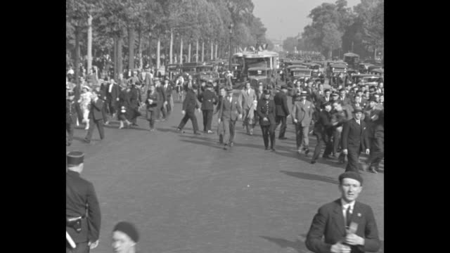 vidéos et rushes de people run in the street some wielding canes with policemen interspersed trying to clear street for traffic / policemen shove and move a man along /... - 1934