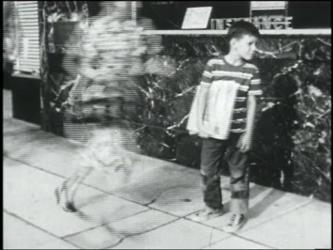 b/w 1950 people run on sidewalk past paper boy / man grabs paper boy / air raid - crowd running scared stock videos & royalty-free footage