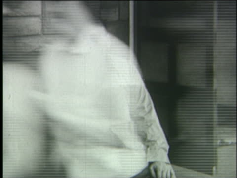 b/w 1951 people run past blind man sitting by wall during air raid - 1951年点の映像素材/bロール