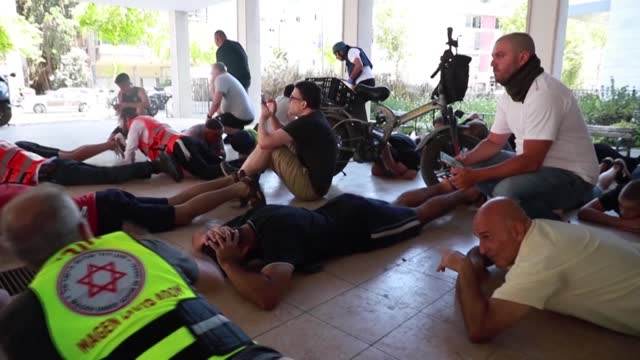 stockvideo's en b-roll-footage met people run to take cover as sirens ring warning from an incoming rocket fired from the gaza strip, and israeli security forces and emergency services... - israël