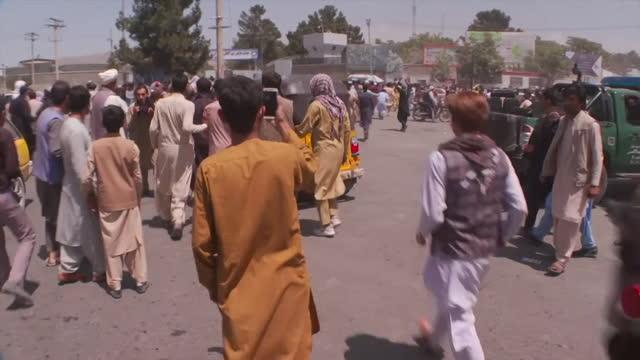vídeos y material grabado en eventos de stock de people run towards airport in kabul to flee afganistan as taliban take over the city, gun shots fired into air - kabul