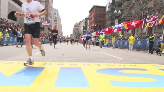 vidéos et rushes de / people running across the boston marathon finish line prior to the bombing. - bombardement