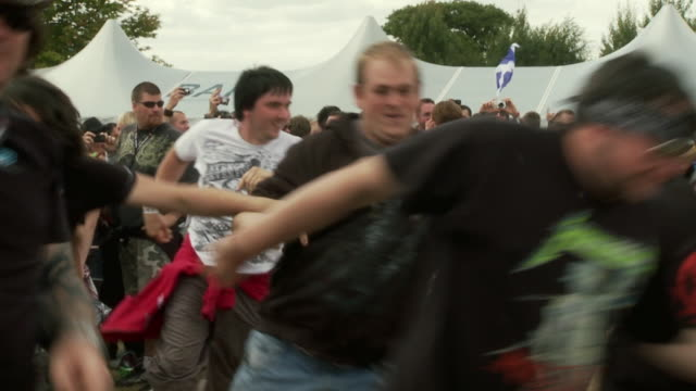 vídeos de stock e filmes b-roll de ms pan slo mo people running and cheering around in circles at sonisphere festival / knebworth, hertfordshire, uk - bater com a cabeça