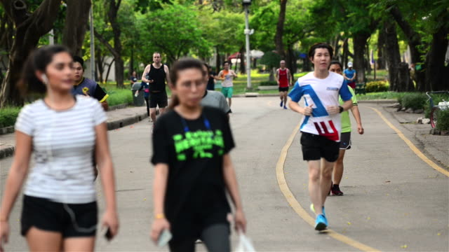 People running and jogging along a paved road in Lumpini park
