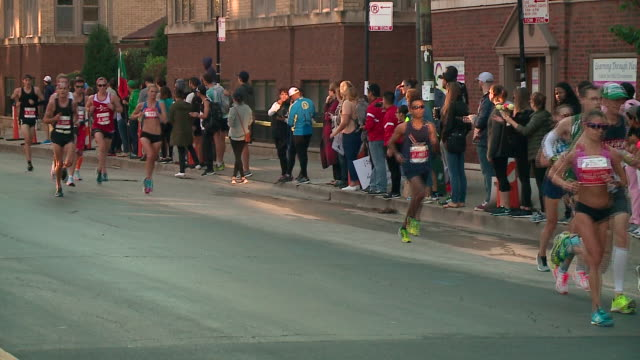 people running in the 2017 chicago marathon at the intersection of west addison street & north broadway on oct. 8, 2017. - ランニングショートパンツ点の映像素材/bロール