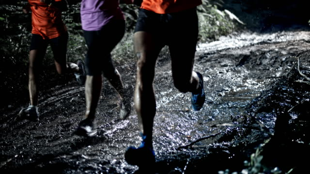 SLO MO DS People running on a muddy forest trail at night