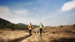 People running on a sunny mountain trail