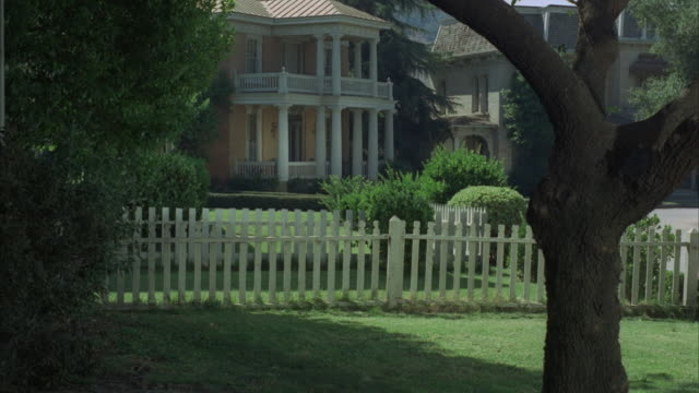 vidéos et rushes de ms, people running on lawn at large colonial style mansion, jumping over fence - clôture