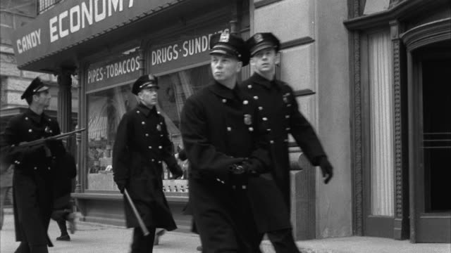 1953 B&W MS People running on street, police officers walking in opposite direction
