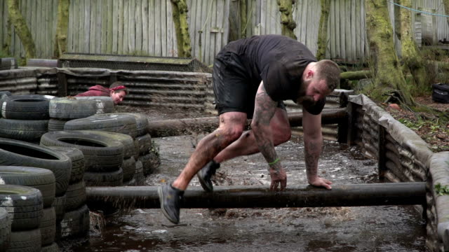 vídeos de stock e filmes b-roll de people running through water in mud run obstacle course / assault course - slow motion - lama solo