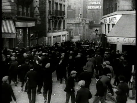 vidéos et rushes de people running throwing things in narrow street gendarmes running on sidewalk chasing people up road people rioting in street one injured male walking - 1934