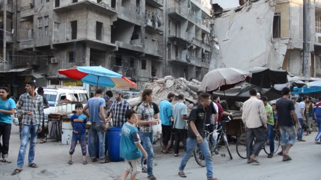 people rush to buy food to break their daylong ramadan fast at a historical bazaar which is heavily damaged by asad regime forces' attack in shear... - シリア点の映像素材/bロール