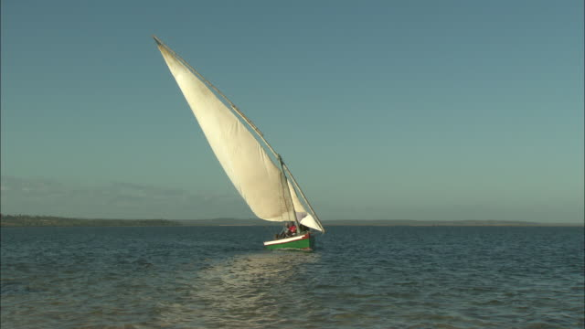 vídeos de stock e filmes b-roll de people sail a dhow across the zambezi river delta.  - barco à vela