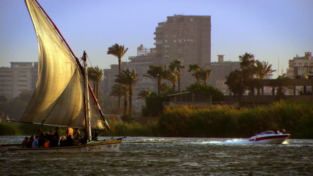 people sail in a traditional dhow along the waterfront of cairo. - ダウ船点の映像素材/bロール