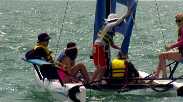 people sailing in a small catamaran in miami, florida - life jacket stock videos & royalty-free footage