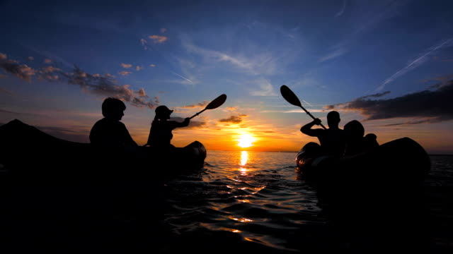 ts people sea kayaking at sunset - canoeing stock videos and b-roll footage