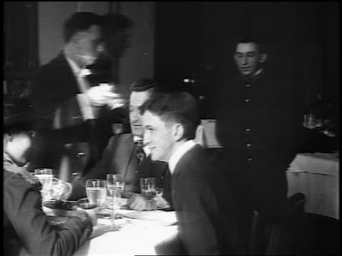 vídeos y material grabado en eventos de stock de b/w 1916 people seated at table in restaurant toasting + drinking / man offers other cigarette - 1910