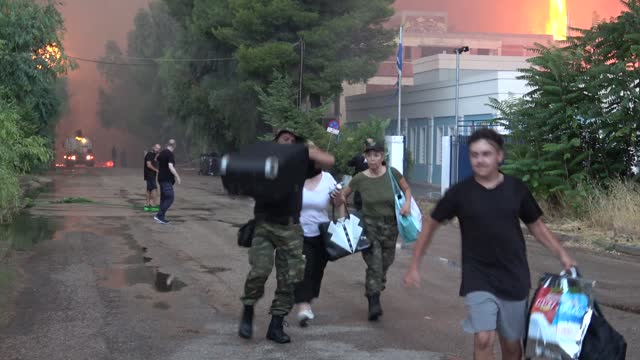 """people seen evacuating their homes, after they were ordered by police, while a house with a greek flag is seen burning, during wildfires in the """"nea... - greece stock videos & royalty-free footage"""