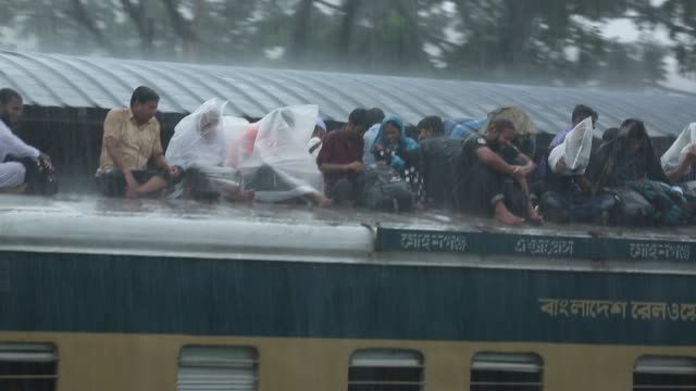 people seen traveling rooftop on an train during torrential rain leaving for their hometowns for the upcoming festival eid aladha at the airport... - climate disaster stock videos & royalty-free footage