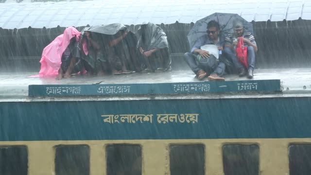 people seen traveling rooftop on an train during torrential rain leaving for their hometowns for the upcoming festival eid aladha at the airport... - bahnreisender stock-videos und b-roll-filmmaterial