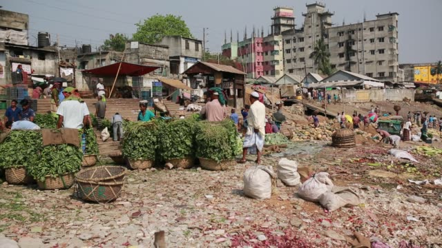 People sell vegetables in wholesale market near Buriganga river in Dhaka Bangladesh on March 21 2018