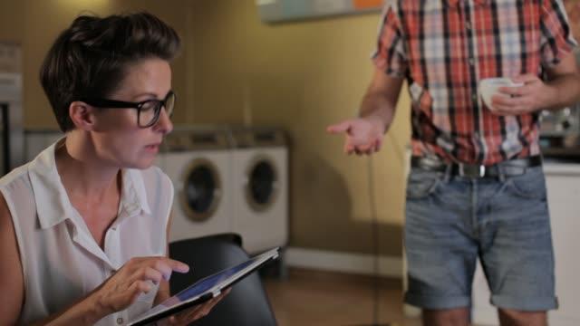 people sharing digital tablet - launderette stock videos & royalty-free footage