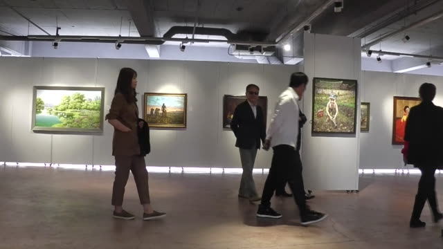 people shop at a north korean art gallery in dandong, china. art is sold in china to fund the north korean government. - kunst, kultur und unterhaltung stock-videos und b-roll-filmmaterial