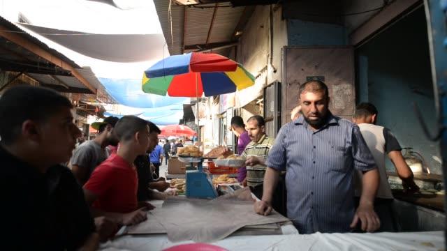 people shop for the the islamic holy month of ramadan in gaza city, gaza on may 28, 2017. - 日常の一コマ点の映像素材/bロール