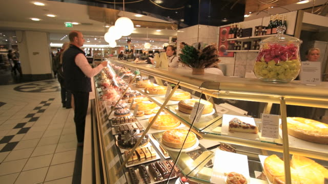 People shopping at KaDeWe food department store-Cakes and delicacies from all over the world